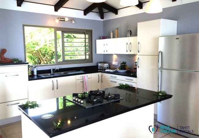 Equipped kitchen of the Villa Vahineria Dream, open on the dining room, view of the lagoon, vacation rentals in Tahiti