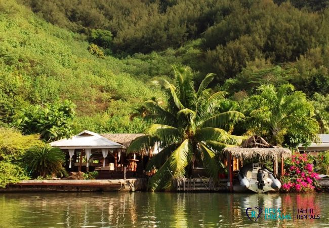 View of the Villa Tiahura from the lagoon, surrounded by palm trees in the sun of French Polynesia, in Moorea