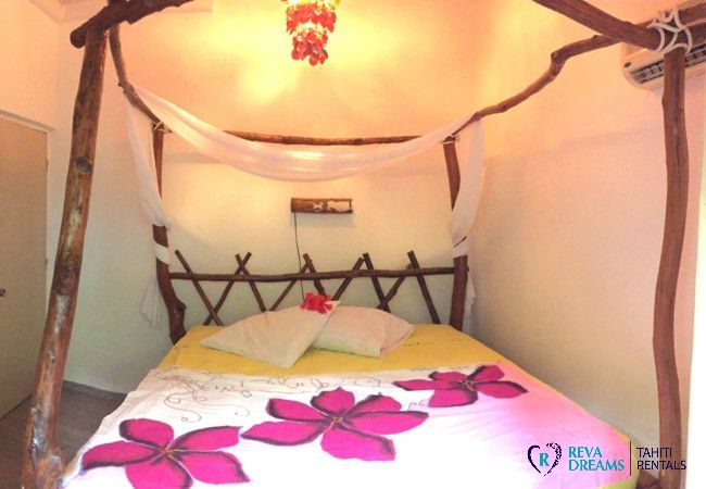 Double bedroom, wooden local decoration, at the Villa Tiahura, stays and trips by the seaside on the island of Moorea