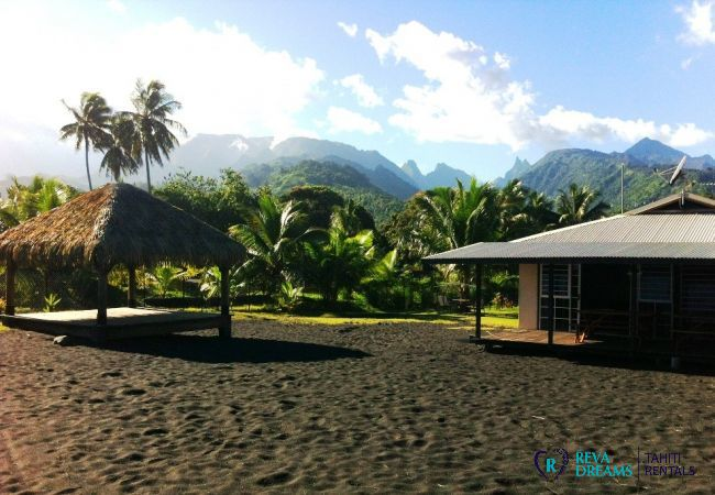 Garden and beach with fare pote'e of the Fare Taharuu, holidays between sea and mountains in Tahiti, French Polynesia