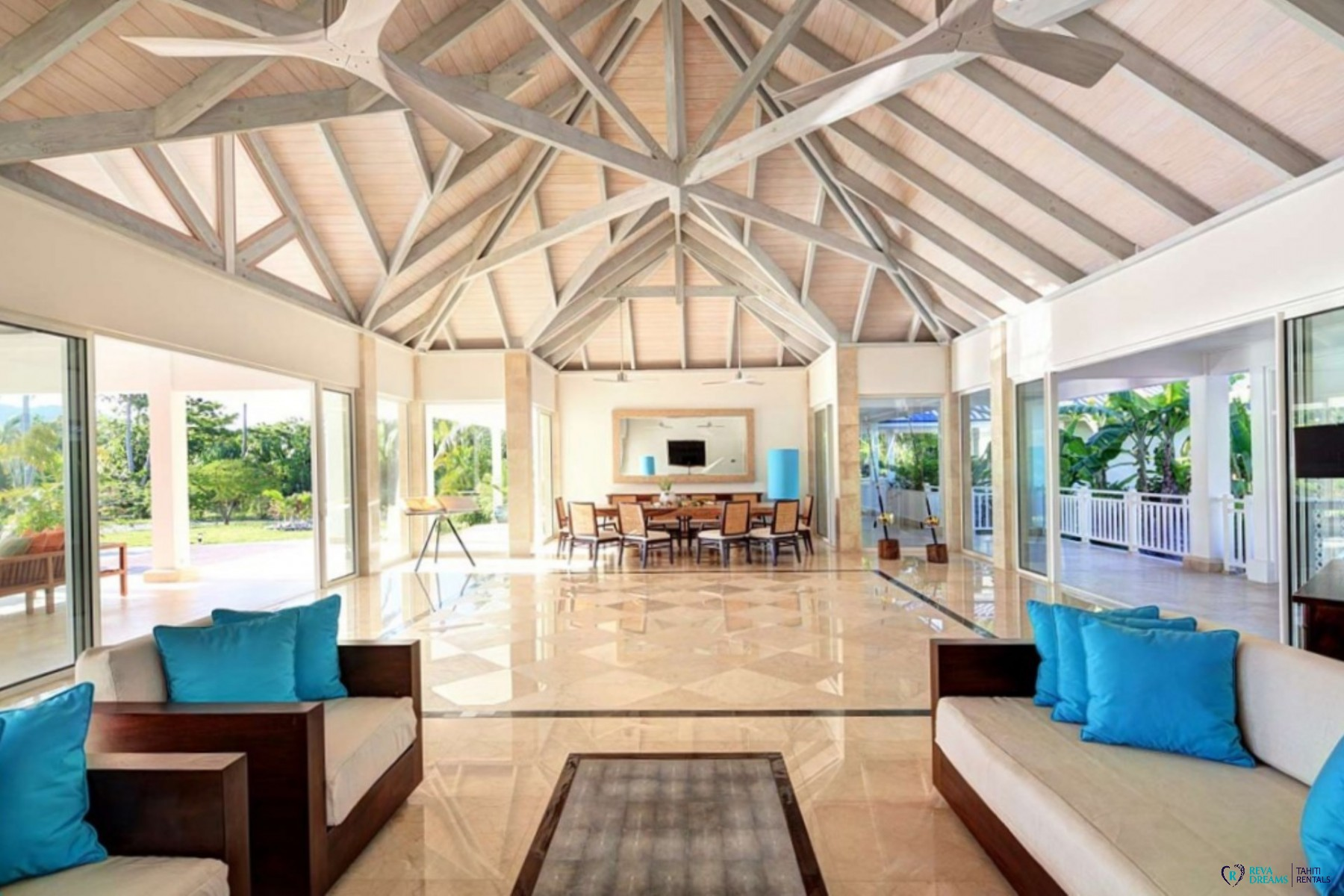 Large living room of villa deluxe bora bora with lounge and dining room overlooking the sunny