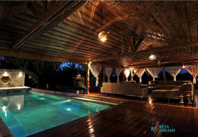 Terrasse et piscine de nuit, décoration typique polynésienne, vacances de rêve sur l'île de Moorea