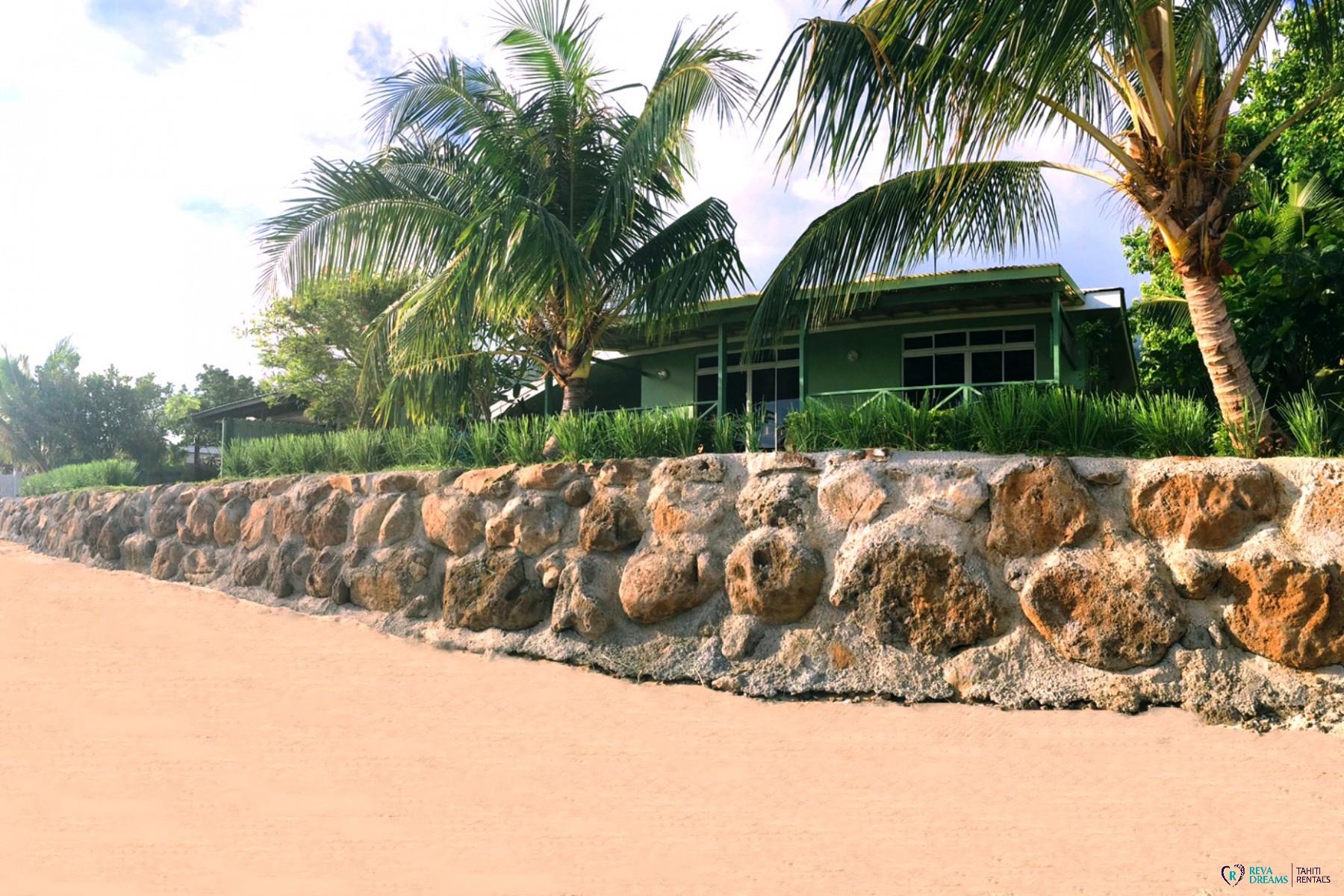 Vue du Fare Taina Nui depuis la plage de sable blanc, séjours et vacances sous les palmiers de Polynésie Française