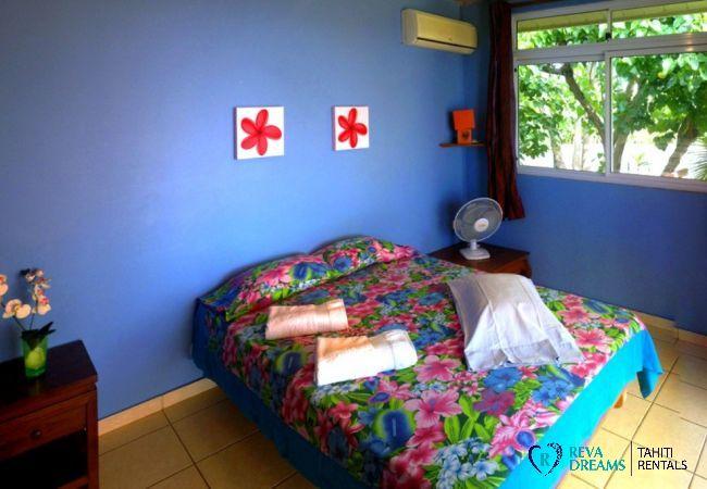 Chambre avec lit double et décoration tropicale au Fare Taina Nui, maison de vacances à Moorea, près de Tahiti