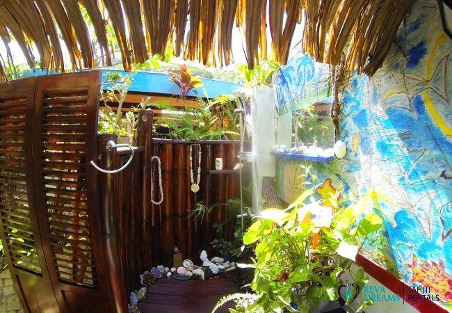 Douche polynésienne en bois, entourée de coquillages et plantes tropicales au Fare Aroha Ho'e, séjours à Bora Bora