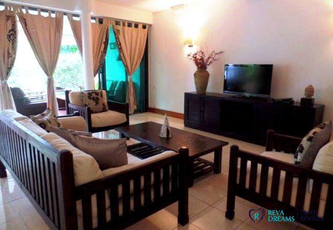 Salon avec accès au jardin tropical, location de vacances à l'appartement Carlton Plage de Tahiti en Polynésie Française