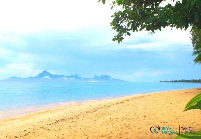 Vue sur Moorea, île sœur de Tahiti, depuis la plage de sable blanc de la résidence de l'appartement Carlton Plage