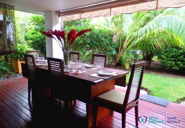 Terrasse et coin repas au bord du jardin tropical, location de vacances à l'appartement Carlton Plage à Tahiti