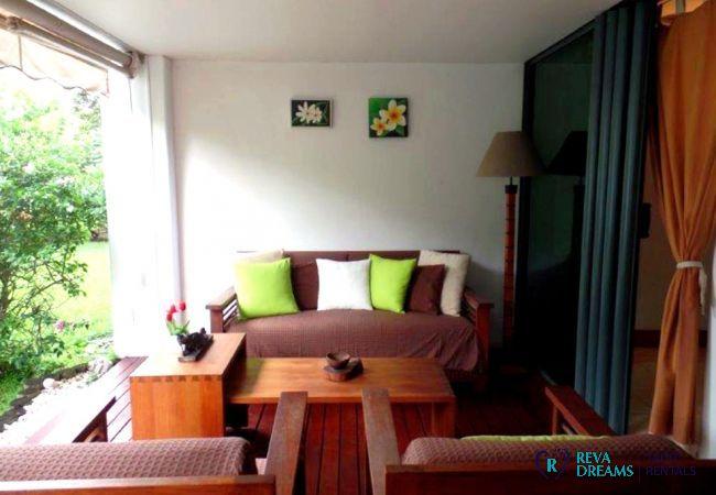 Terrasse et salon avec accès au jardin tropical et à la piscine, à l'appartement Carlton Plage à Tahiti