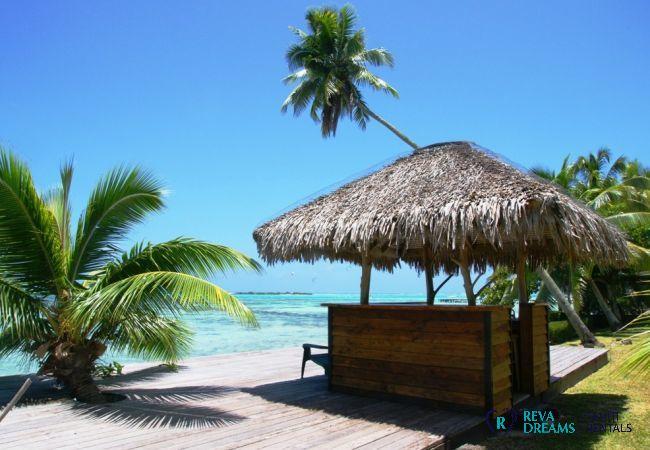 Bar de plage tropicale ombragée par des palmiers, avec une vue sur le lagon à la Villa Teareva Dream