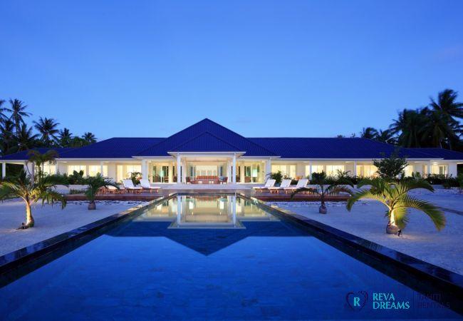 Piscine de la Villa Deluxe Bora Bora en Polynésie Française, à la nuit tombée avec vue sur l'entrée éclairée de la Villa.