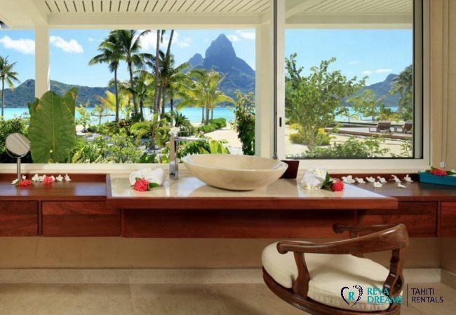 Salle de bain de la Villa Deluxe Bora Bora, avec vue sur le lagon, les palmiers et le mont Otemanu