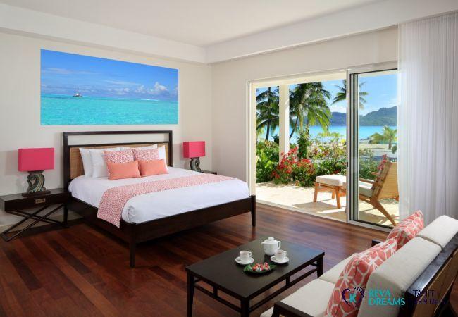 Chambre de la Villa Deluxe Bora Bora, avec terrasse privée, vue sur les cocotiers et la mer bleue turquoise