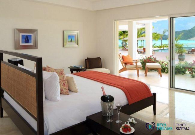 Chambre de la Villa Deluxe Bora Bora avec terrasse, vue sur la piscine d'eau de mer, le lagon et le mont Otemanu