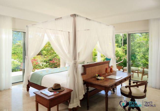 Chambre de la Villa Deluxe Bora Bora en Polynésie Française, avec lit à baldaquin, bureau en bois et terrasse privée