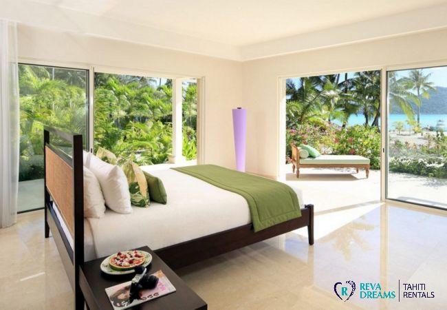 Chambre de la Villa Deluxe Bora Bora en Polynésie Française avec terrasse, vue sur les palmiers et le lagon