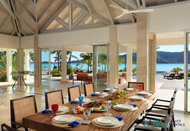 Salle à manger de la Villa Deluxe Bora Bora, donnant sur la terrasse, la piscine à débordement et le lagon