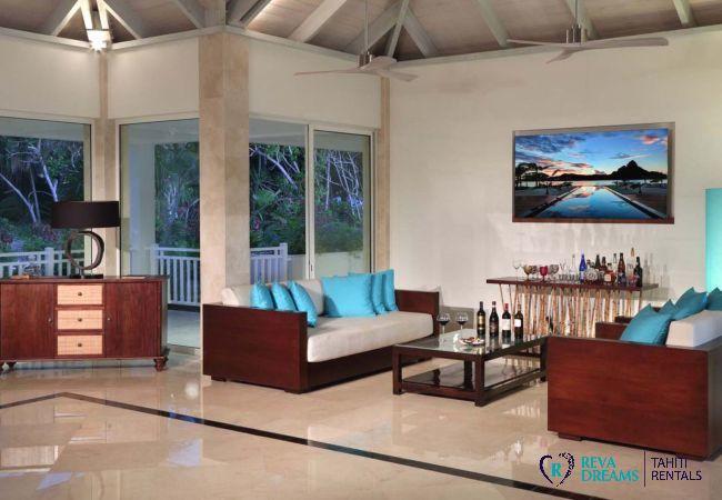 Salon de la Villa Deluxe Bora Bora en Polynésie Française équipé de plusieurs canapés et d'un buffet