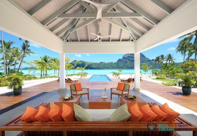 Terrasse de la Villa Deluxe Bora Bora, entourée d'un deck en bois exotique, avec vue sur le lagon et le mont Otemanu